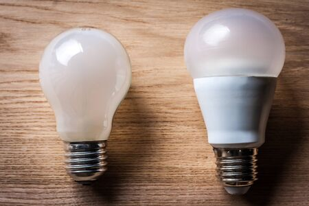 oppose: incandescent and LED lamp on wooden table Stock Photo
