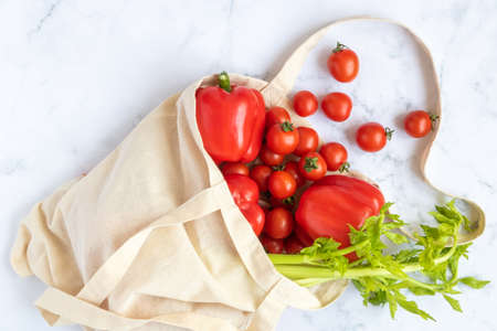 Linen bag reusable with vegetables: celery, red bell pepper, cherry tomatoes on a marble background. Concept - a world without plastic. Stok Fotoğraf