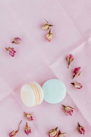 Top view at macarons and dried roses on pastel color bakcground. Standard-Bild - 140552959