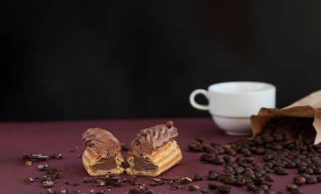 Still life made from pieces of eclair filling with chocolate cream, beans of coffee and blurred white cup at dark background. Copy space.