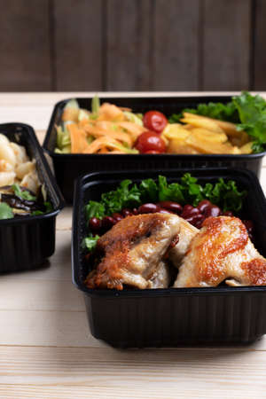 fried chicken wings with micro greens, stewed vegetables in food containers Stock Photo