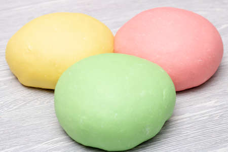 green pink and yellow dough lying together