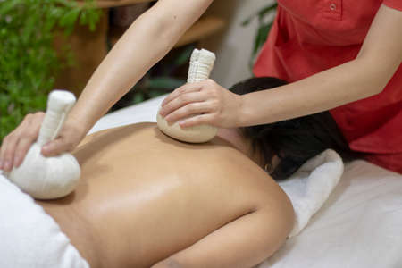 Thai massage for back, healthy herbla compress