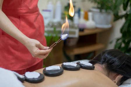 setting zen basalt stones on back massage Stock Photo