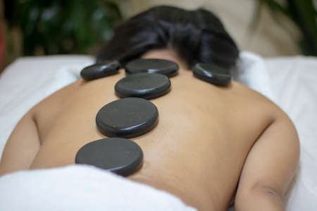 Back massage with hot stones. Woman relaxing Stock Photo