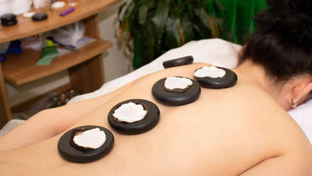 Young woman enjoying a hot rock massage in a spa salon as heated basalt stones are placed on her muscles prior to commencing the massage.