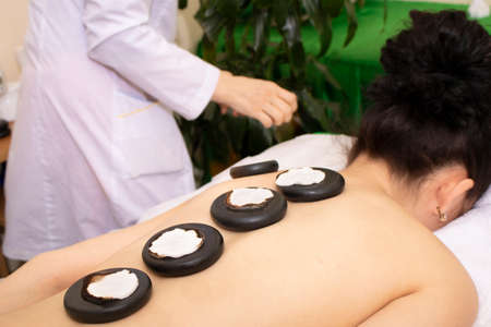 Girl on a stone therapy, hot stone massage. Restorative procedure for body and soul - basalt stone massage Stock Photo