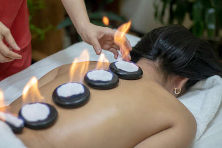 Massage basalt hot stones of woman in spa salon. Girl on candles background has stone therapy and skincare in spa salon. Luxary interior in therapy. Stock Photo
