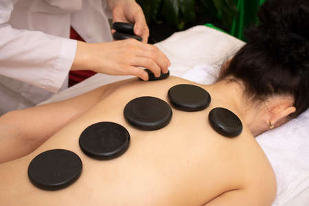 Massage with hot basalt stones. Beautiful deep charming light