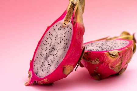 Colorful fruits pattern with Pitahaya tropic fruits, two halfs of fruit on a pastel pink background, copy space. Close up