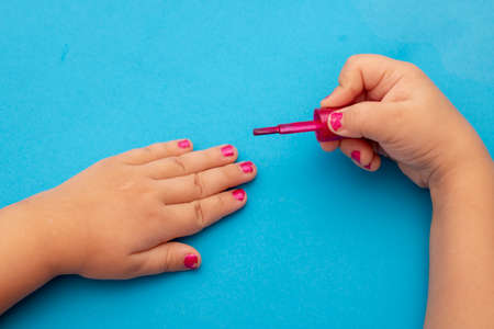 children's manicure. Children's hands paint their nails with Colorful nail polish. Red manicure on childish nails.