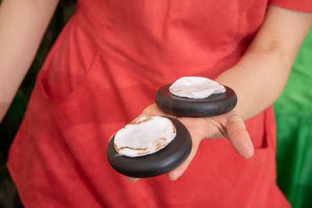 Hot basalt stones are used for a luxurious hand massage relaxing neglected and overworked hands. Finish with buff polish. Stock Photo