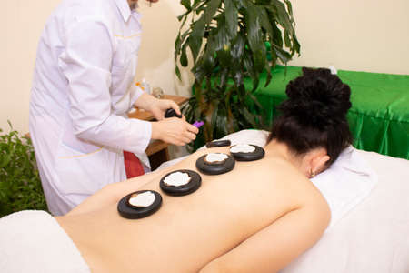 Beautiful Woman Getting Spa Hot Stones Massage in Spa Salon.