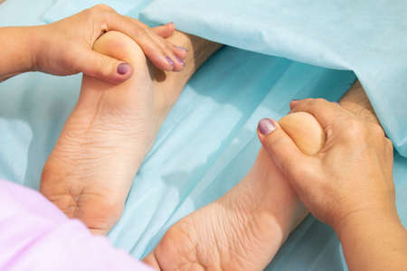 Close-up of female hands doing foot massage.feet relaxing thai therapy Stock Photo