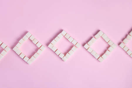 close up of white crystal sugar cubes on pink background, flat lay sweet