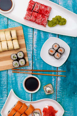 Delicious set of variation sushi rolls with traditional soy sauce and chopsticks on asian plates, flat lay on blue wooden rustic background. Vertical orientation