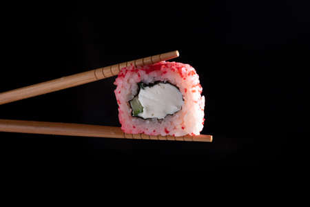 Chopsticks holding seaweed pink rice roll filled with avocado and cheese over dark background, copy space