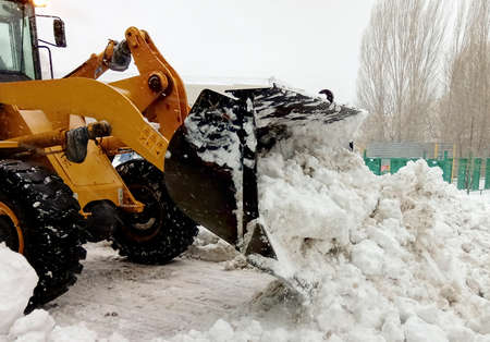 Big machine cleaning the snow from the road in the yard