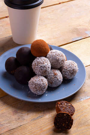Healthy energy organic balls with sesame seeds, coconut and a cup of coffee Archivio Fotografico