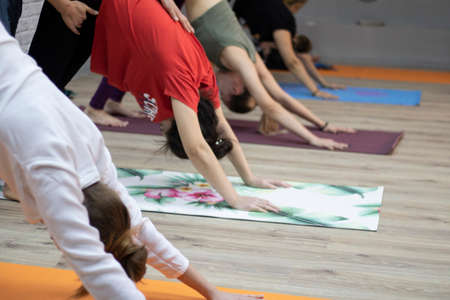 Young people doing yoga in club with coach