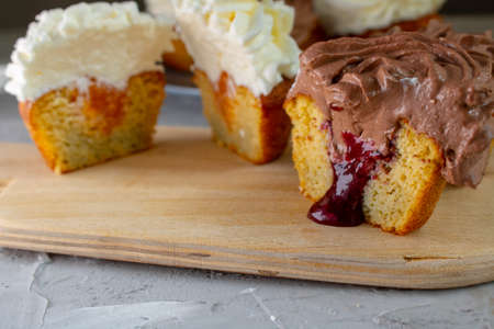Yellow and chocolate cupcakes with jam on kitchen board. No gluten Stok Fotoğraf