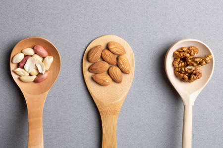 Three wooden spoon with almonds, peanuts and walnuts. Top view