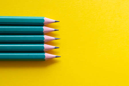 Set of black pencils on yellow background, view above