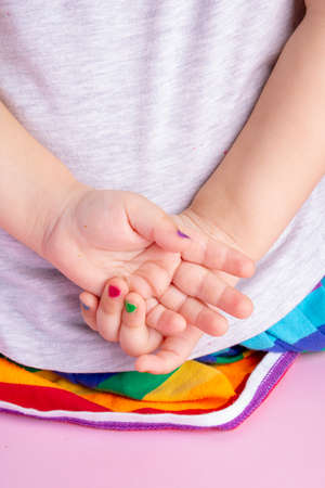 little girl hands with colorful manicure behind back, vertical image