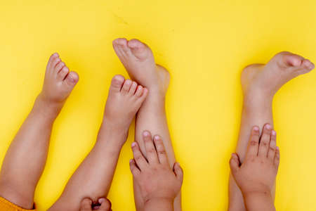Kids Legs on yellow paper, flat lay. Childhood concept