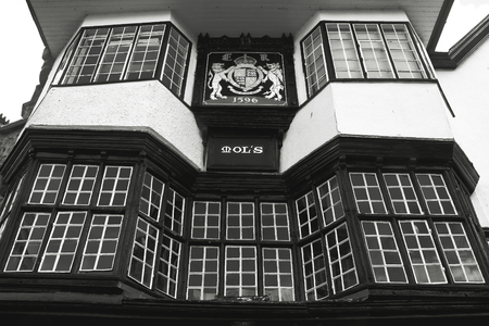 house coat: EXETER, UK, 11 July 2016: Facade of an ancient building in the center of Exeter. Mol`s House, 1596. The coat of arms of the city. Black and white photography. Devon. England Editorial