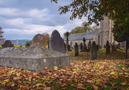 tombstones: Graveyard near the church. Autumn. Fallen dry leaves lying on the ground. The clouds in the sky. Chagford. Dartmoor. Devon. UK