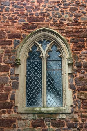 Une fenêtre dans un cadre magnifique. Mur de pierre d'une ancienne église anglaise Banque d'images