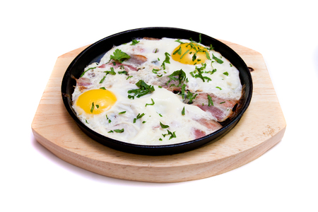 fried eggs with bacon in a frying pan on a wooden stand