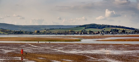 People walk along the river bottom Exe. Low tide. Exmouth. Devon. England