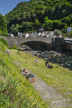 lyn: Lynmouth, North Devon, England, July 13, 2016: People relax by the river in the village of Lynmouth. Editorial