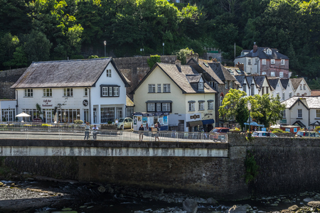 lyn: Lynmouth, Devon, England, 13 July 2016: The bridge across the river across the West lyn. People walk by the bridge. Many houses. Cafes and small shops. Editorial