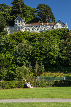 lynmouth: Lynmouth, Devon, England, 13 July 2016: Tors Hotel on the hill and people have a rest at the bottom on the bench