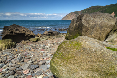 lynmouth: Beach with large boulders at low tide. Boulders covered with algae. In the background you can see the sea. Near the Lynton and Lynmouth villages. North Devon Coast. UK