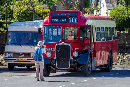lynmouth: Lynmouth, Devon, England, 13 July 2016: tourist makes a photograph of an old English bus