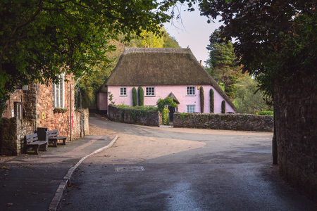 Cockington, Devon, England. A large classic Devonian house with a thatched roof with the village of Cockington. Location near Torquay.
