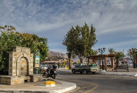 toyota: Elounda, Crete, Greece, 19 September 2013: Coastal street. Parked motorcycle and Toyota car Editorial