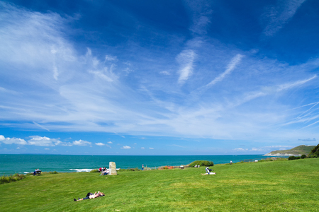 Woolacombe, Devon, England, 14 July, 2016:  People are lying on the lawn or are sitting. Enjoy the good weather by the sea