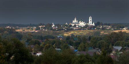 Nikitsky monastery in Pereslavl-Zalessky. Ancient Russian monastery. The temple is brightly lit by the low sun against a dark cloud. Yaroslavl region. Russia