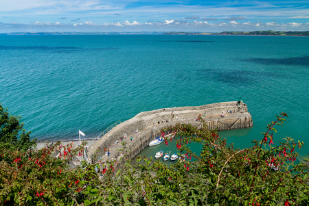 An ancient stone pier near the village of Clovelly. Several boats are moored. People are walking on the pier. View from above. Devon. England
