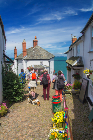 Several tourists stand on a paved path and admire the beauty of the village of Clovelly. This picturesque English village is located on the steep seashore in Devon. Tourists have a dog. Along the path there are many bright flowers. England