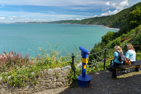 Clovelly, Devon, England, July 14, 2016: Two women sit on a bench and enjoy a beautiful view. View point.