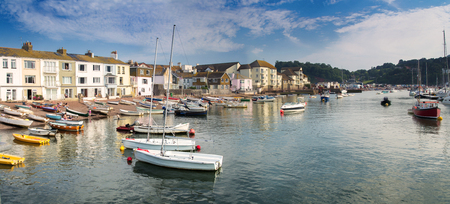 Panorama of the coast in the town of Teignmouth. Some people rest on the beach. Swim boats after a days work. Stock Photo