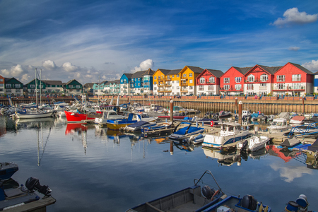 A small and cozy harbor in the town of Exmouth. There are many vessels moored here. Around the harbor are colorful beautiful houses. Devon. England Stock Photo