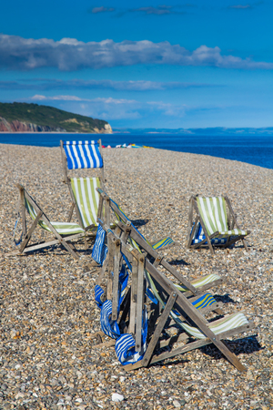 Deck chairs on the pebble beach in the fishing village of Beer. Devon. UK