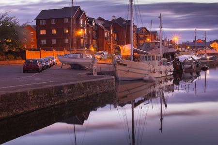 Harbor on the channel of the river Exe. Quiet evening. Sunset. Street lighting works. Yachts and boats are moored. Exeter. Devon. UK
